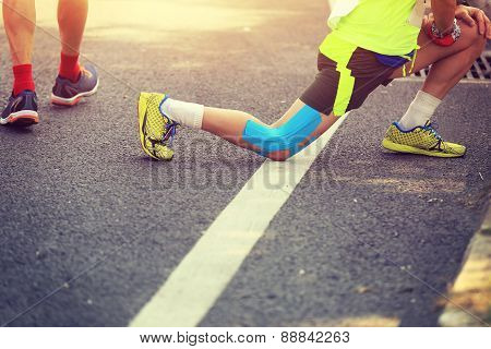 marathon runner stretching legs on road
