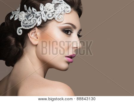 Portrait of a beautiful woman in the image of the bride with lace in her hair.