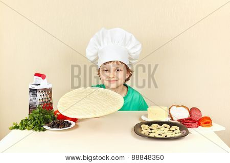 Little boy in chef hat at the table with ingredients is going to cook pizza
