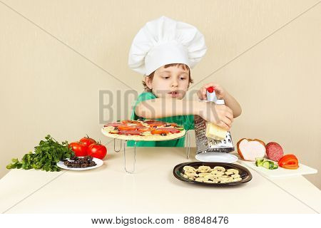 Little boy in chefs hat rubs on grater cheese for pizza