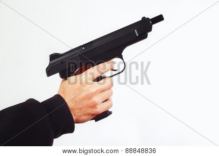Hand with discharged semi-automatic handgun on white background