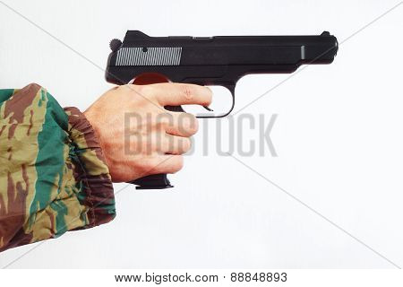 Hand in camouflage uniform with army pistol on white background