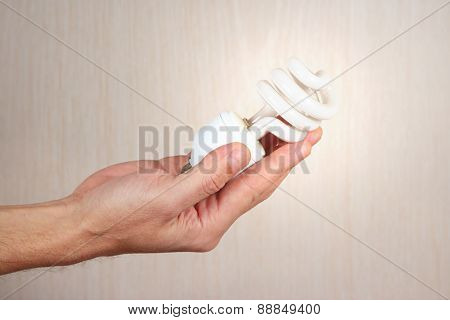 Hand holding a glowing tungsten lightbulb on light wood background