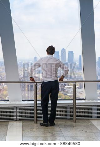LONDON, UK - APRIL 22, 2015: Businessman looking at London through the window of Walkie-Talkie build