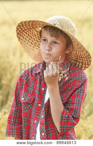 Careless Teenage Farm Boy In Wide-brimmed Hat Chewing Oat Cereal Ears Straw