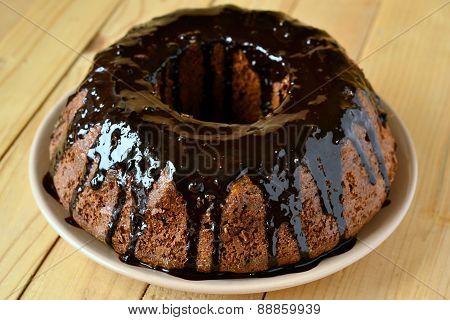 Banana fruitcake with dried apricots in chocolate glaze