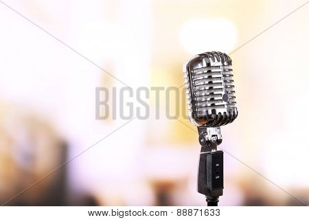 Retro microphone on bright blurred background
