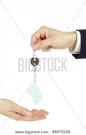 Male hand giving key with trinket to female hand isolated on white
