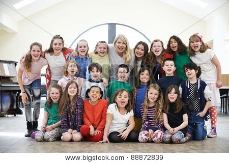 Large Group Of Children With Teacher Enjoying Drama Workshop Tog