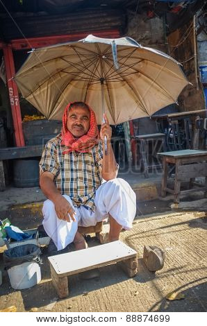 MUMBAI, INDIA - 10 JANUARY 2015: Indian worker sitting under a parasole on sidewalk
