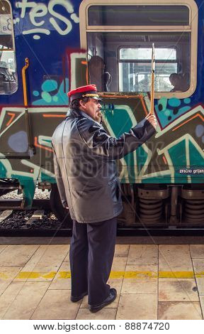 ZAGREB, CROATIA - 17 MARCH 2015: Controler signaling to the train driver with his wistle and sign to mark the departure on platform number 1 in Glavni kolodvor (main train station).