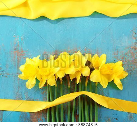 Beautiful bouquet of yellow daffodils on wooden background
