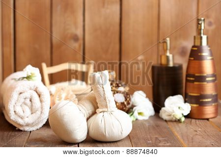 Beautiful spa composition with massage bags on wooden background