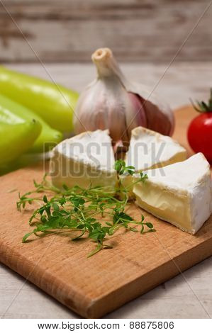 Cress Shoots In Front Of Camembert Portions