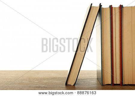 Old books on wooden table isolated on white