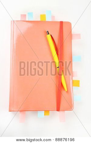 Notebook with bookmarks and pen, isolated on white