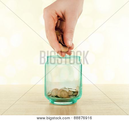Female hand putting coins in glass bottle on bright blurred background