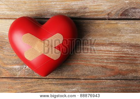 Heart with plaster on wooden planks background