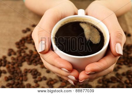 Female hands holding cup with coffee beans on burlap cloth, closeup