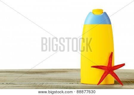 Bottle of suntan cream with sea star on table isolated on white