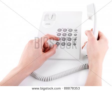 Female hand holding phone receiver and dialing number isolated on white