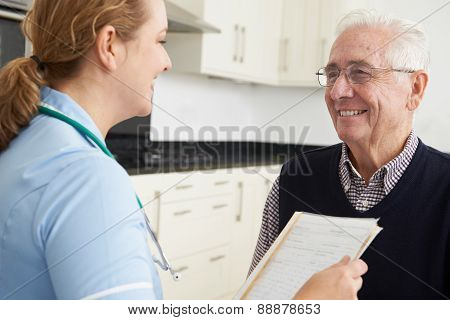 Nurse Discussing Medical Record With Senior Male Patient