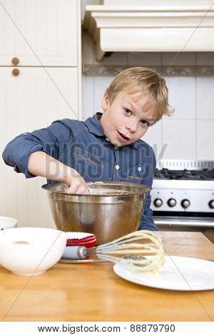 Young child wiping pastry dough from a stainless steel bowl with his finger whilst making cupcakes