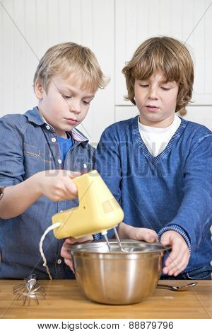 Two friends mixing dough in a stainless steel bowl using a mixer, during a baking workshop for kids at a kitchen counter