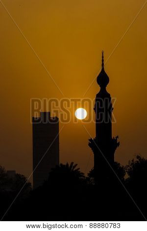 Cairo, Egypt -  Silhouettes of a minaret and skyscraper at sunset