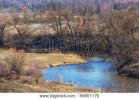 Fisherman Catches Fish On A Rod On The River Bank In A Sunny Day In The Early Spring