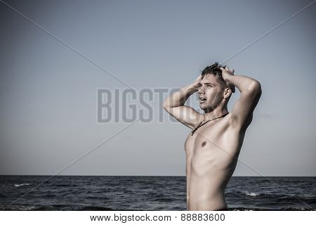 Attractive Young Man In The Sea Getting Out Of Water With Wet Hair