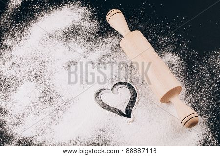 Flour with heart and rolling pin on black background