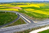 image of rape-seed  - Aerial view of road passing through a rural landscape with blooming rape in northern Greece  - JPG