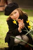 stock photo of overcoats  - A pretty young blonde girl of four dressed in a brown overcoat trousers and beret is holding a yellow daffodil with one hand and stroking it with the other - JPG