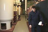 foto of boiler  - maintenance engineer checking technical data of heating system equipment in a boiler room - JPG