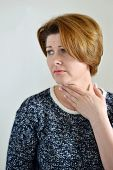 stock photo of throat  - Adult woman with a sore throat on a light background - JPG