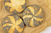 image of bap  - close up of three poppy seed rolls on greaseproof paper - JPG