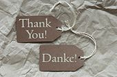 foto of thankful  - Two Brown Labels Or Tags With White Ribbon On Crumpled Paper Background With German Text Danke Means Thank You And English Thank You Vintage Or Retro Style - JPG