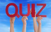 stock photo of quiz  - Many Caucasian People And Hands Holding Red Straight Letters Or Characters Building The English Word Quiz On Blue Sky - JPG
