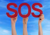 picture of sos  - Many Caucasian People And Hands Holding Red Straight Letters Or Characters Building The English Word Sos On Blue Sky - JPG