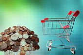 stock photo of grocery-shopping  - Shopping trolley and coins on green tone background - JPG