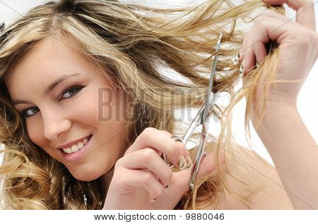 Smiling Young Woman Cutting Hair With Scissors