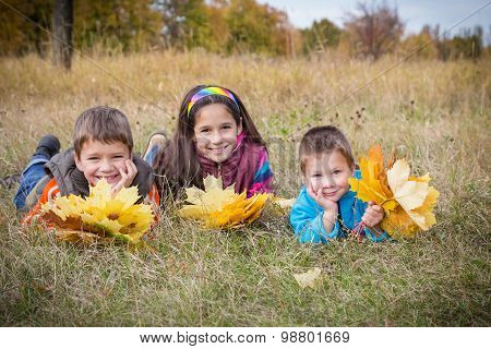 three kids with autumn leaves