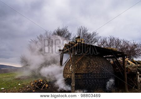 Traditional coal making process on a cloudy autumn day