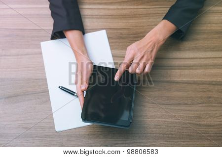 Closeup Of A Business Woman's Hands While Browsing In The Tablet And Looking For The Essential Infor