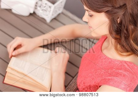 Top view of woman reading book in cafe