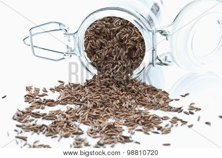 Caraway Seeds Spilling From Glass Jar On White Background