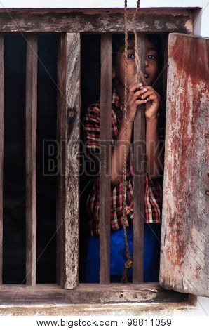 Unidentified Indian boy looks through window at home