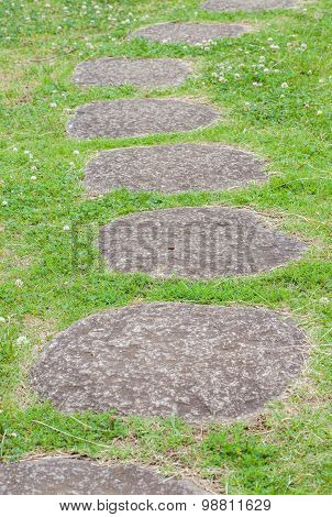 Zen stone path and green grass in a Japanese Garden