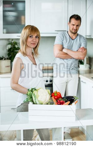 Woman With Vegetable Box In Kitchen, Man Looking Sceptical